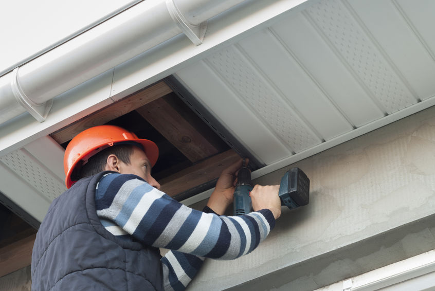Construction worker mounting soffit insulation.